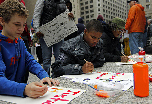 Protesters make signs during a rally for Trayvon Martin in Daley Plaza on Saturday.