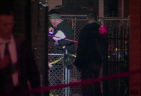 Chicago police search a back yard where a man was shot by an officer late Friday, (WGN-TV)