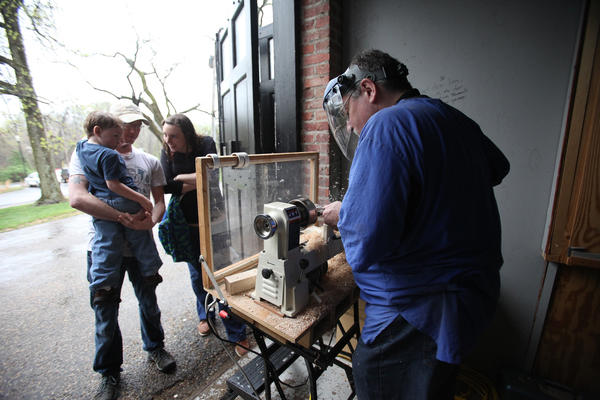 Jeramy Brian, of Towson, holds his son Jack Brian, 3, while they and his wife, Susanna Brian, watch Ted Rudie, of Glen Burnie, spin a wooden top during a Chesapeake Woodturners demonstration at The Carriage House at Montpelier Mansion in Laurel.