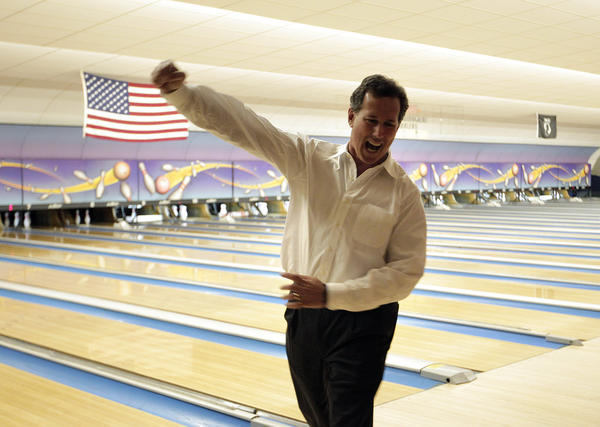 Rick Santorum, who won Saturday's Republican presidential primary in Louisiana, celebrates a strike while bowling after a campaign rally in Sheboygan, Wis.