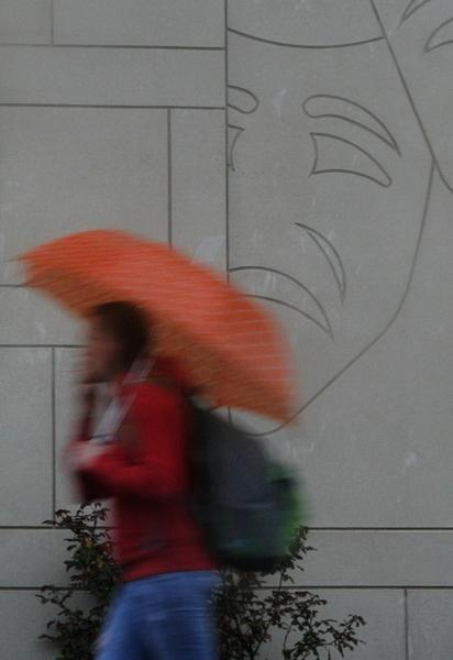 A pedestrian finds shelter beneath an umbrella as she passes Freeman Center on a dreary rain filled morning.