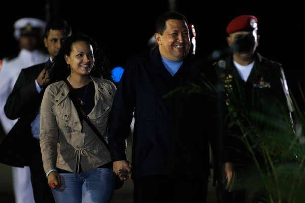 Venezuelan President Hugo Chavez walks with his daughter Rosa Virginia during his departure to La Habana, Cuba, where he will begin his radiation therapy sessions, at the Maiquetia Airport in Caracas.