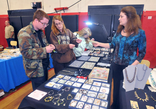 New Moon Creations owner Debra Cross of Alburtis (right) helps Peter Clarkson of Palmerton and his mother Pam Weldon of Palmerton look for jewelry, during the Saucon Valley Lions Club's Lehigh Valley Gem and Mineral & Jewelry Show at the Saucon Valley High School gym on Sunday.