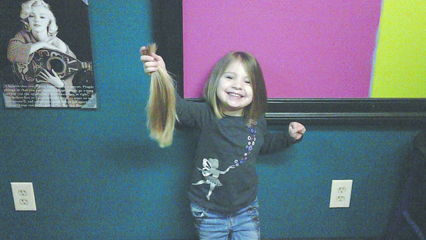 Eliza Byrd, 3, holds a portion of her hair that was cut to send to the Locks of Love program, which provides wigs for children who have lost their hair due to illness.