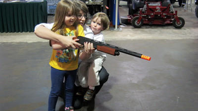 Benjamin and Abigail Bergquist enjoy some target practice at a plastic deer with a rubber dart gun while at the 2012 Mega Show Sunday. Benjamin, 2, and Abigail, 3, are pictured with their mother, Alison, of Champion.