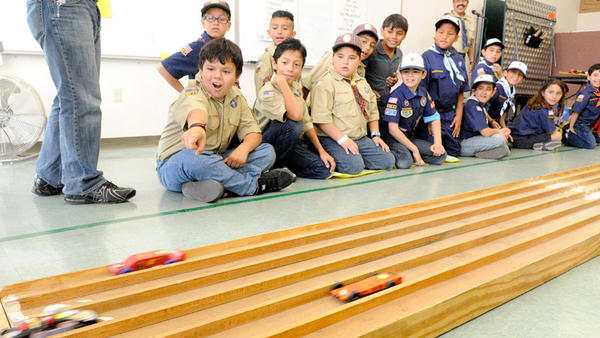 Members of Boy Scouts Pack 4005 watch and cheer on as pinewood derby races get under way Saturday in Calexico.