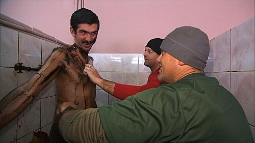 In Detour B in Baku, Azerbaijan, Border Patrol Agents JJ (center) and Art must scrape and scrub the oil off a hairy man with a creepy expression.