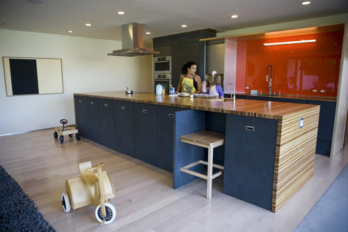 "The kitchen is the heart of the house for Klauber-Speiden, who loves to cook and entertain.  ""The kids can run outside, and I can see them wherever they are,"" she says. The kitchen also has ""space for everything."" There are no upper cabinets; all storage is underneath the counter, behind doors made of recycled rubber.  Klauber-Speiden says she saved $7,000 by going with an induction cook-top rather than buying gas and installing a new gas line. To create the orange backsplash, Klauber-Speiden painted the back of clear glass instead of buying more expensive colored glass."