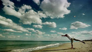 A man practices yoga on the beach in Ocean Ridge. Expect a mostly sunny, breezy Tuesday.