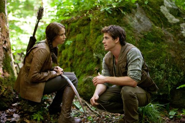 "Jennifer Lawrence portrays Katniss Everdeen, left, and Liam Hemsworth portrays Gale Hawthorne in a scene from ""The Hunger Games."""