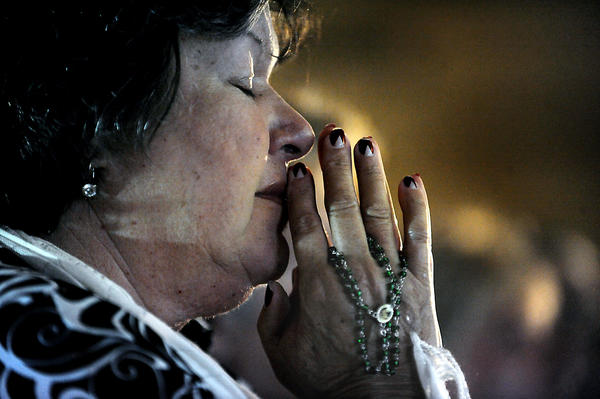 Esperanza Santana holds her rosary as she prays while watching the mass in Cuba of Pope Benedict XVI at the Shrine of Our Lady of Charity. Santana came to the U.S. from Cuba in 1970.