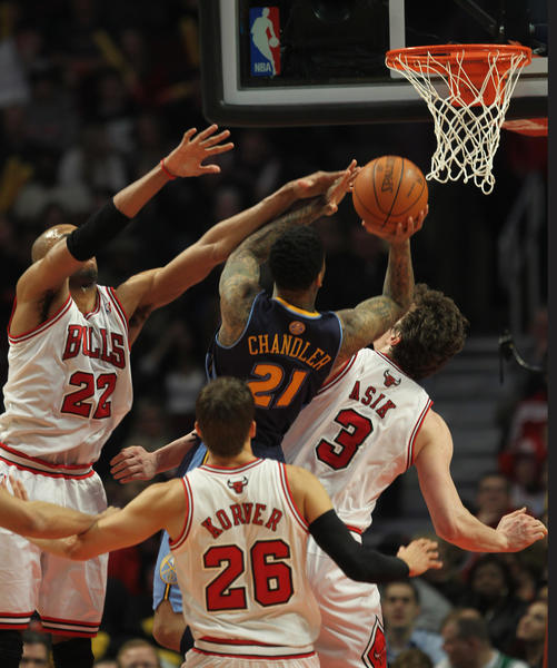 Wilson Chandler takes on a trio of Bulls during the Nuggets victory Monday.