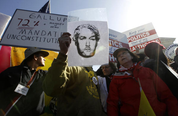 An image of the late conservative media publisher and activist Andrew Breitbart is held up as opponents of President Obama's health care reform plan rally in front of the Supreme Court in Washington on Tuesday as the court continued hearing arguments on the legislation.