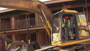 Demolition has begun on a former motel where a South Side pastor camped out for three months. WGN-TV