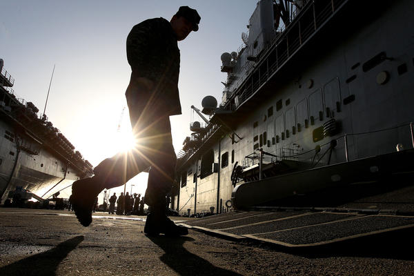 Sailors board the USS Iwo Jima early Tuesday morning as the ship prepares to deploy from Naval Station Norfolk.