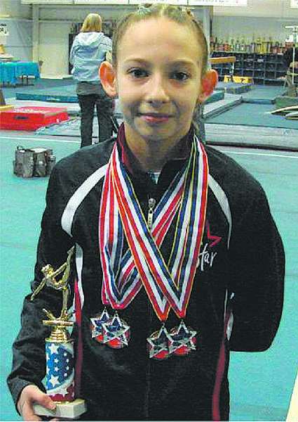 Faith Wilson displays the trophy and medals she won at a recent gymnastics meet.