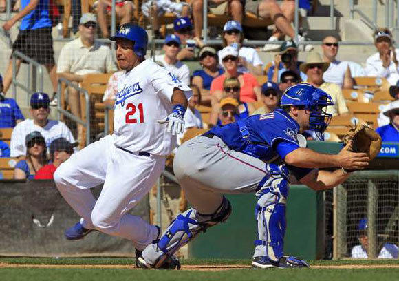 Juan Rivera scores past Texas Rangers catcher Chris Robinson in the sixth inning of a spring training game on March 16.