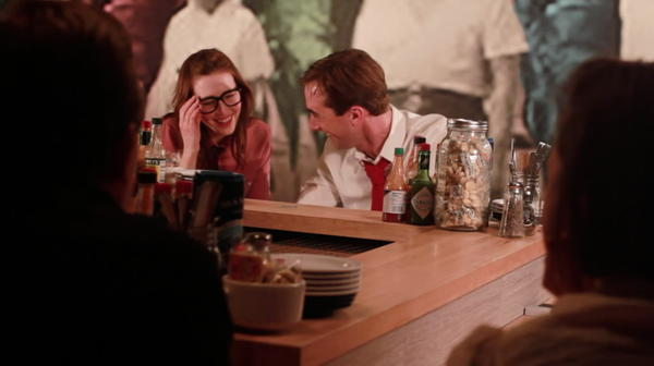 "Martine Moore (Chloe) and Chris Mathews (Chip Waddle) getting a drink after a hard day of rocket science, from the theater-film mashup ""I Am a Rocket Scienctist."""