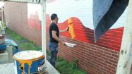 An artist is honoring an injured Marine from Ararat by painting an American flag on a building.