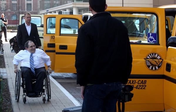 Joe Russo, center, prepares to board one of several wheelchair accessible cabs parked at McCormick Place. The 47 new wheelchair accessible cabs added to the city's fleet will operate on compressed natural gas.