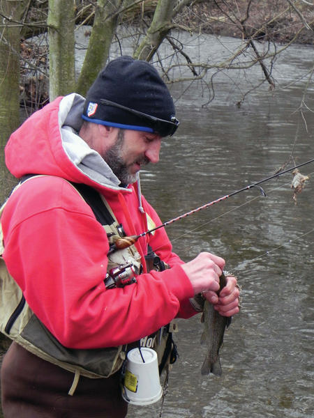 Mark Hollinshead of Orrtanna, Pa., examines a fish he caught in Conococheague Creek in Chambersburg, Pa., during opening day of the 2011 trout season in Franklin County.