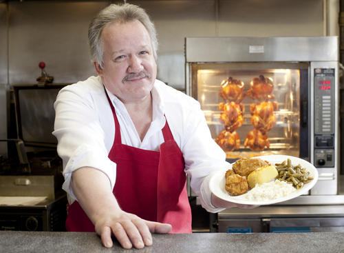 Tom Cooley, owner of Harvest Fried Chicken in Woodbine, holds a chicken plate in the restaurant's kitchen. Cooley was formerly the meat manager at a Woodbine grocery store, and offers catering services as well. His largest catering order to date was 800 pieces of chicken.