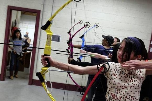Isla Herrera, 12, right, prepares to fire a bow during lessons at Archery Bow Range on Tuesday in Chicago.
