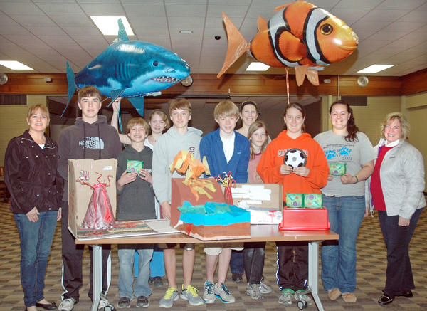 "Pictured above showing just some of the items that were purchased for middle school science classes are (from left) Charevoix Schools Foundation board president Pam Barnes, middle school students Austin Putman, Jonathon Pischner, Hannah Ennis, Alex Kleiber, Ben Boss, middle school science teacher Amy Pott, Irah Dhaseleer, Madyson Wojan, Skylar Herriman, and foundation board member Sue Herzog. Many of the items shown above are part of the ""teaching with toys"" curriculum Pott uses in her classroom to illustrate scientific principles."