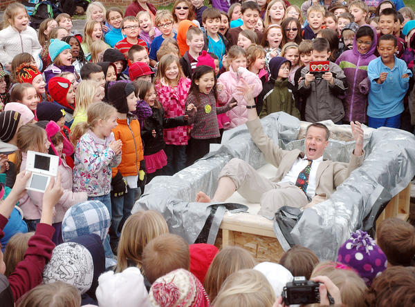 Charlevoix Elementary School students react as their principal Doug Drenth falls into a vat of Oobleck as their reward for meeting the school's March Into Reading goal for this year.