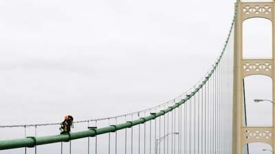 A Mackinac Bridge steeple jack changes lights on the structure Thursday.
