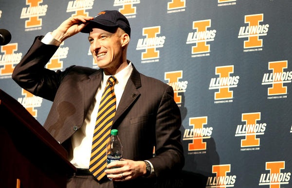 John Groce puts on an Illini hat as he is introduced as the new Illini head men's basketball coach at Assembly Hall in Champaign, Ill.