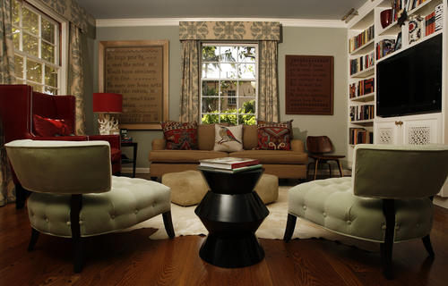 The living room, with its witty mix of vintage flavor and contemporary furniture. Note the embroidery artwork on the back wall.