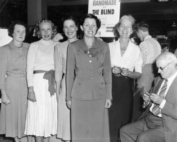 Foothill Service Club for the Blind member Walter Dorrance, right, demonstrated his leather craft skills at a 1951 sale of items made by members of the club. Oakmont League members organized the event, held at Sears. Oakmont members from left, Alice Van Roo, Lenora Vom Cleff, Pat Mann, Dot Jones and Evelyn Bertram.
