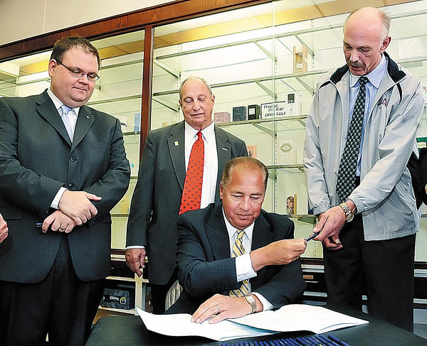 West Virginia Gov. Earl Ray Tomblin hands a pen to state Sen. Herb Snyder, right, on Thursday after signing Senate Bill 437 at Patterson's Drug Store in Martinsburg, W.Va. Also pictured are state Sen. John Unger, left, and Del. John Doyle.