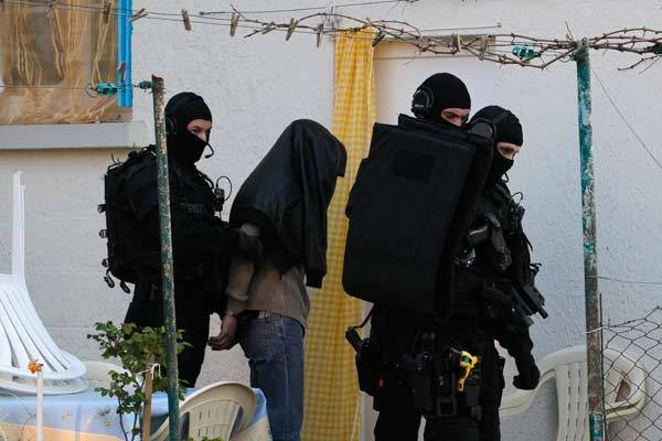 Masked special forces police escort a member of the Islamist community under heavy guard in France.