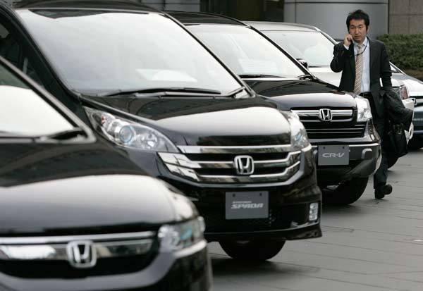 A man walks past Honda vehicles outside a showroom in Tokyo.