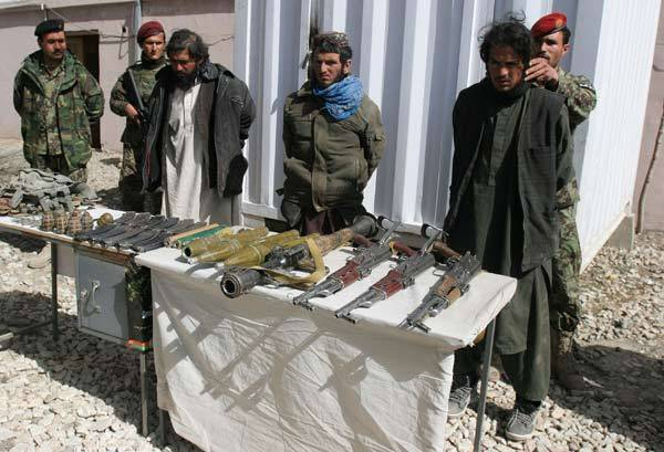 Captured Taliban insurgents and their weapons are presented to the media in Afghanistan.