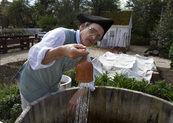 Colonial Williamsburg gardener Wesley Greene shows how a clay thumbpot holds and disperses water for the garden.