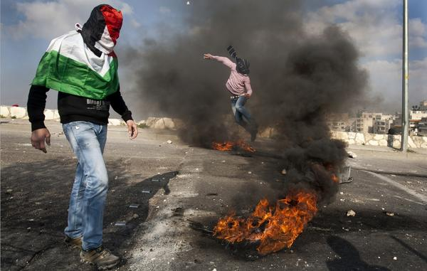 A Palestinian protester throws stones at Israeli security forces during confrontations in the Arab east Jerusalem neighborhood of Issawiya on March 30, 2010, to mark Land Day.