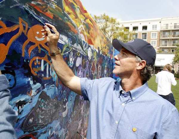 Robert Wyland touches up parts of a mural at the Americana at Brand in Glendale on Friday, March 30, 2012. Community members and Wyland painted a mural that will be displayed at the Americana Anthropologie store to celebrate the 40th anniversary of the Clean Water Act and the upcoming Earth Day.