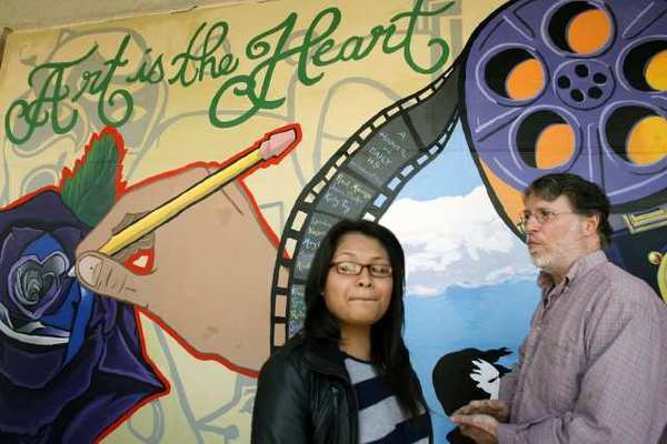 Daily High School student Jennifer Aviles, 18, left, and professional muralist Roger Dolin take a look at a mural during a ceremony, which took place at Hoover High School in Glendale.