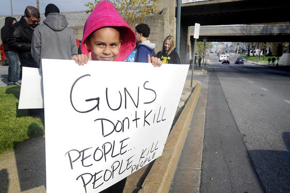 Thailyn Sines, 10, of Hagerstown holds a sign for passing motorists along W. Washington St. to see Friday evening prior to the Hoodie March from the Hagerstown Police Dept to the Public Square.