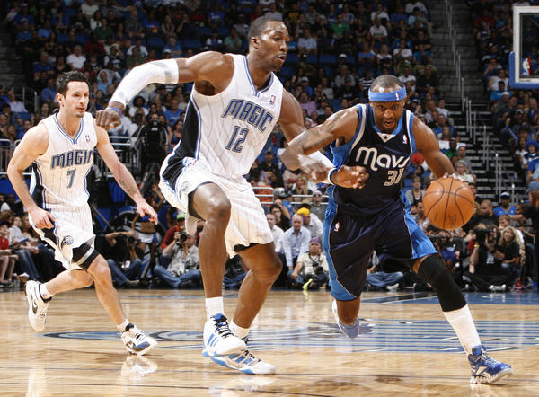 Dallas guard Jason Terry (31) drives past Orlando center Dwight Howard (12) and guard J.J. Redick (7) during the Mavericks' 98-100 victory over the Magic in Orlando, Fla. Friday, March 30, 2012.