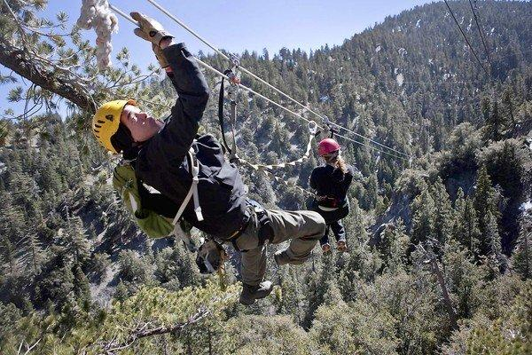 Tour guide Joel Hunt pulls in Jessica Pauline Ogilvie from a zip line in the San Bernardino National Forest.