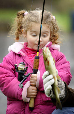"Kayleigh Gasdik, 2, of Allentown admires the 12"" brook trout she just caught while it is being held by her uncle Adam Gasdik of Allentown. They were fishing in the Cedar Creek at Union Terrace.    Trout season opened in Northampton County, Lehigh County and Southeastern Pa. at 8 a.m. Saturday morning."