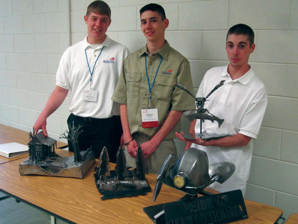 From left, welding students Jon McDaniels, Tanner Butcher and Dillon Swisher show off their metal works of art Saturday at the SkillsUSA Conference at James Rumsey Technical Institute in Hedgesville, W.Va.