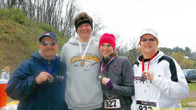 Roxanne and Jack Weighley, far right and far left, and their daughter and son-in-law, Hope and Jay Smetanka of Monroeville, participated as a family at the Meyersdale Maple Race 5K Walk/8K Run on Saturday morning at the Western Maryland Train Station. They each won medals and Hope won third overall best female runner. Hope, a 1999 graduate of Meyersdale, may have been an academic in high school but now she runs four miles a day.