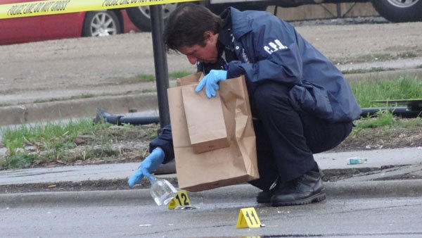 A Chicago Police Department evidence technician works the scene of a shooting on Madison Avenue this morning on the West Side. Four people were hurt in the incident.