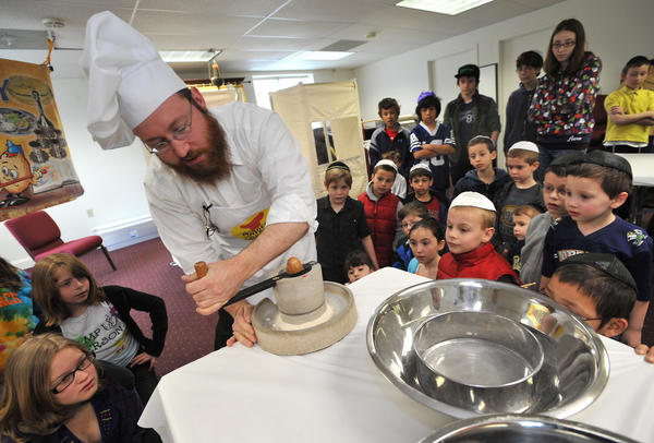 Rabbi Eli Strasberg, of Media, grinds whet into flour during a model matzoh bakery at Chabad of the Lehigh Valley in South Whitehall Township on Sunday, April 1, 2012.  Matzoh which is an unleavened bread, is eaten by Jews  during the Passover Seder meal as well as the the 7 or 8 days of Passover.