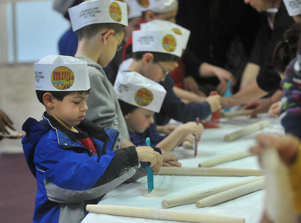 Jack Edelman, 5, of Forks Township (foreground left) rolls dough to make matzoh with youngsters, during a model matzoh bakery at Chabad of the Lehigh Valley in South Whitehall Township on Sunday, April 1, 2012.  Matzoh which is an unleavened bread, is eaten by Jews  during the Passover Seder meal as well as the the 7 or 8 days of Passover.